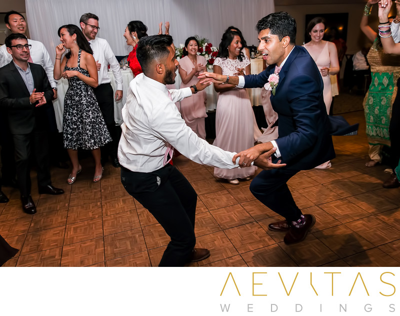 Groom dancing with friend at Pomona wedding reception