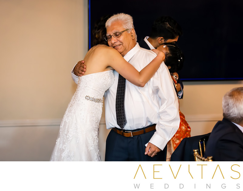 Bride hugs father-in-law at Pomona wedding reception