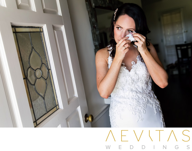 Bride wiping away tears by Sonoma wedding photographer