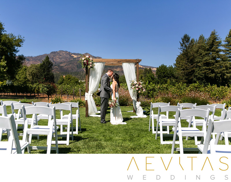 Couple kiss with bridal arch at Landmark Vineyards