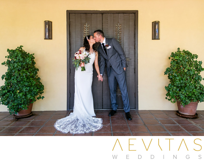 Couple kiss with ornate door at Landmark Vineyards
