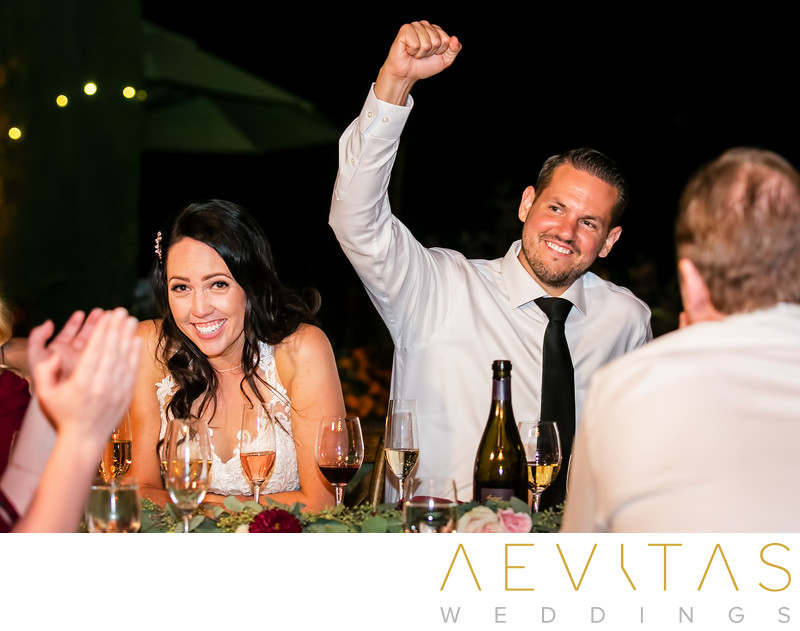 Groom fist pumping and bride laughing at reception