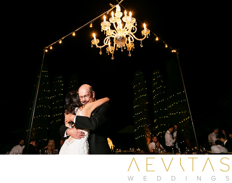 Bride hugs dad beneath chandelier at Landmark Vineyards