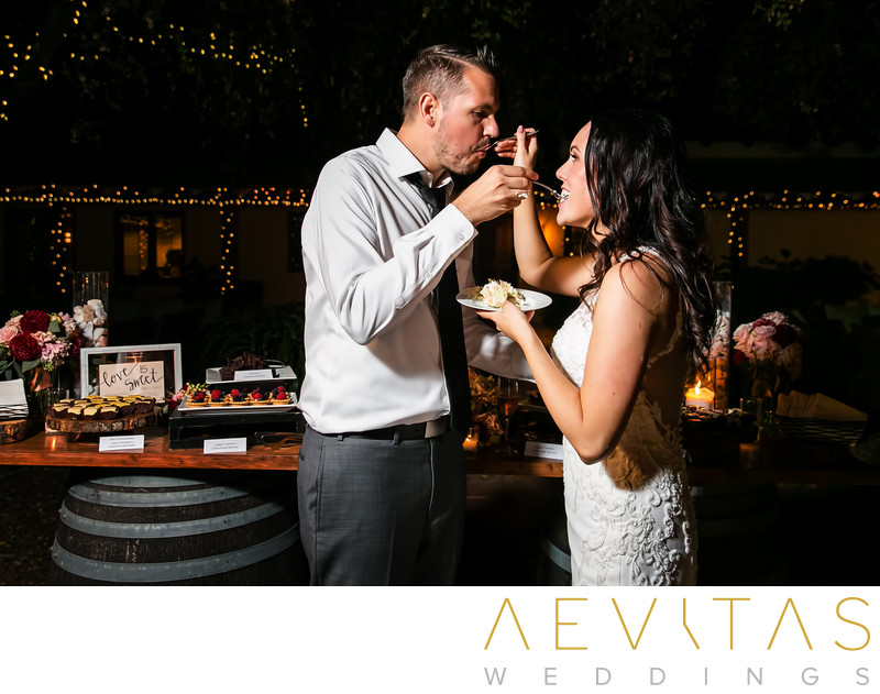 Couple feed one another cake at Landmark Vineyards