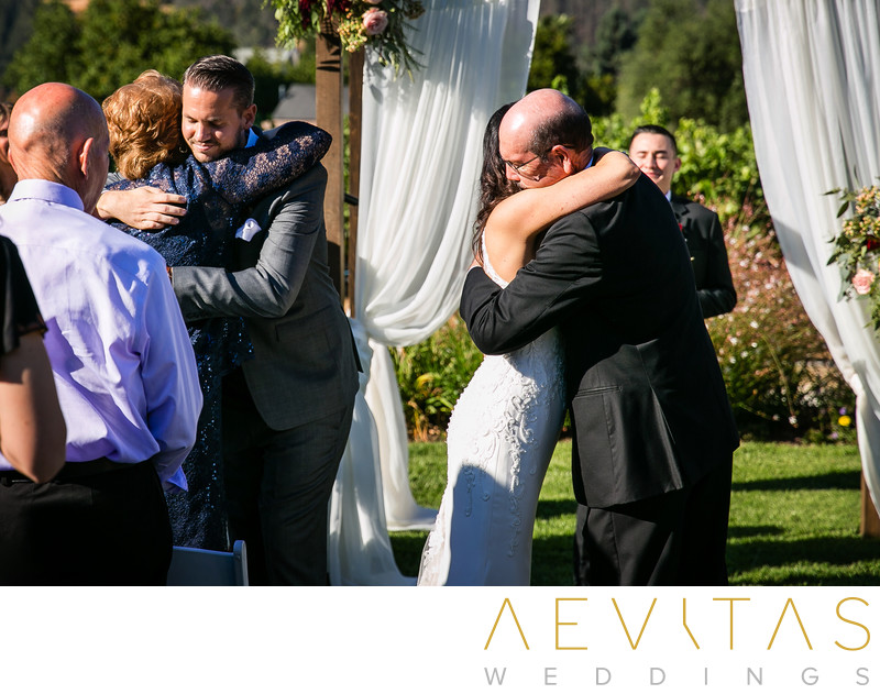 Couple hugs parents at Landmark Vineyards wedding