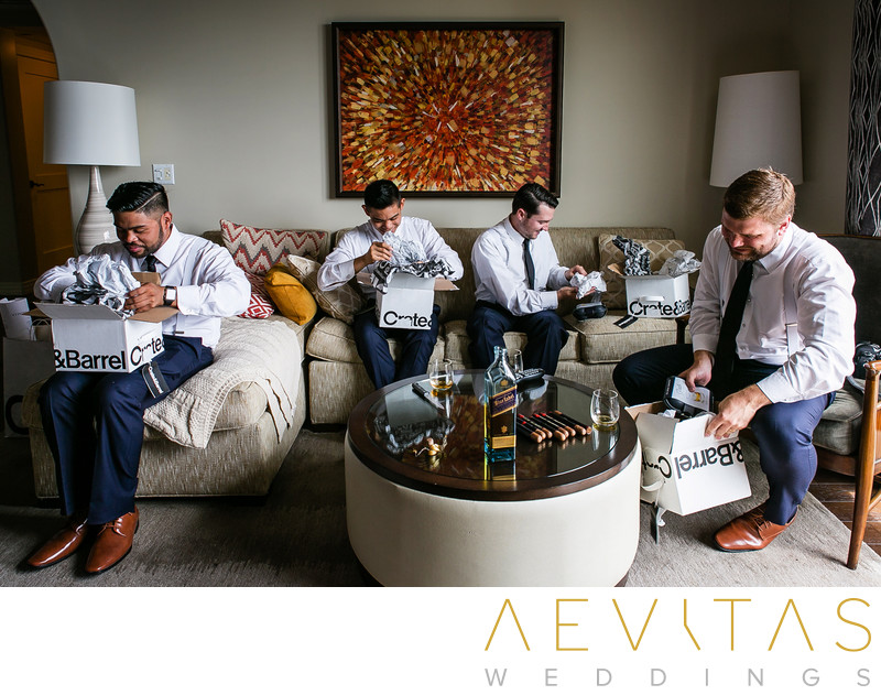 Groomsmen opening gifts in Terranea Resort suite