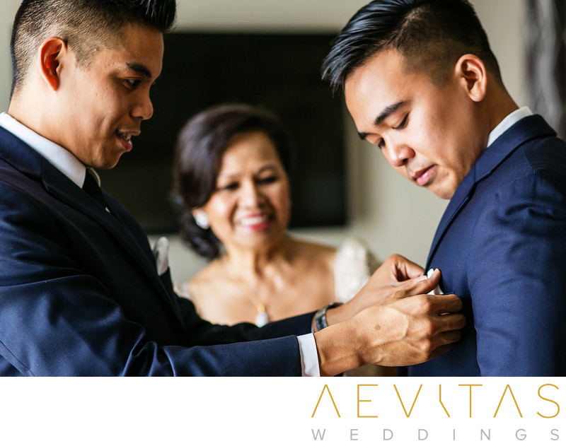 Best man fixing boutonniere with groom's mom