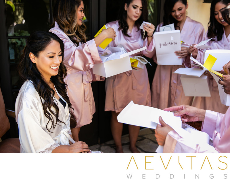 Bride reaction as bridesmaids open gift boxes