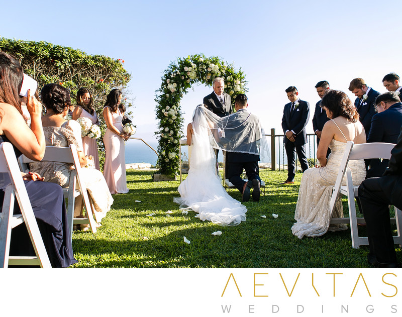 Couple kneel with bridal arch Catholic garden wedding