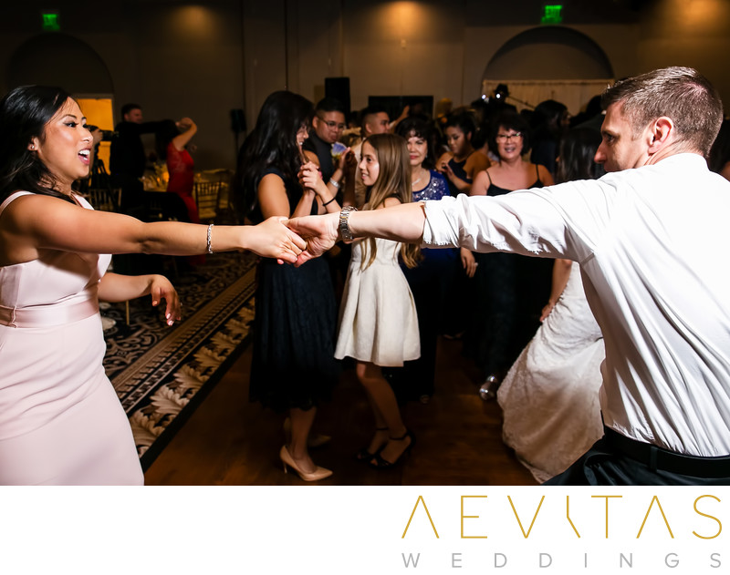 Bridesmaid swing dancing with partner at reception