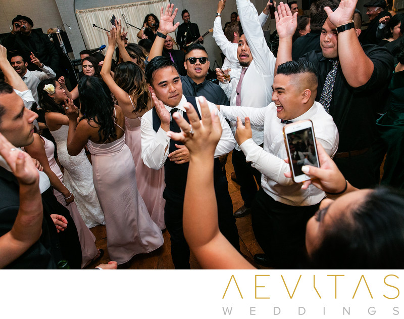 Guests dancing with arms in air at ballroom wedding