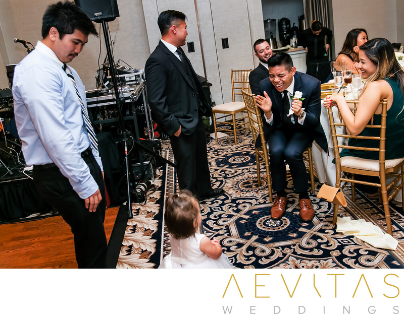 Candid wedding moment between best man and flower girl