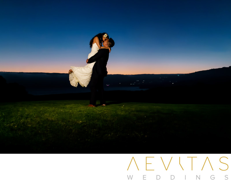 Groom lifts bride during dusk wedding portrait session