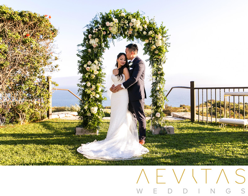 Couple with bridal arch at Trump National Golf Club