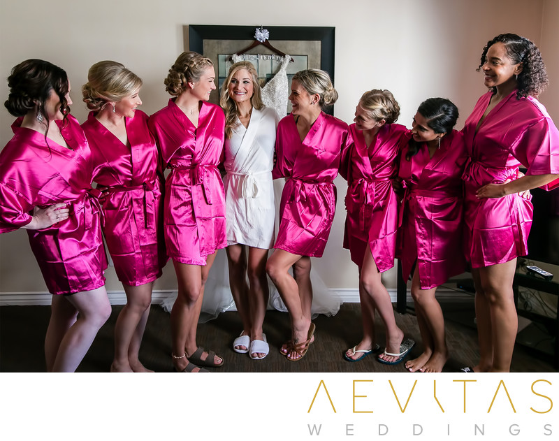 Bride with bridesmaids in hot pink dressing gowns