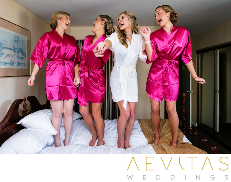 Bride and bridesmaids jumping on hotel suite bed