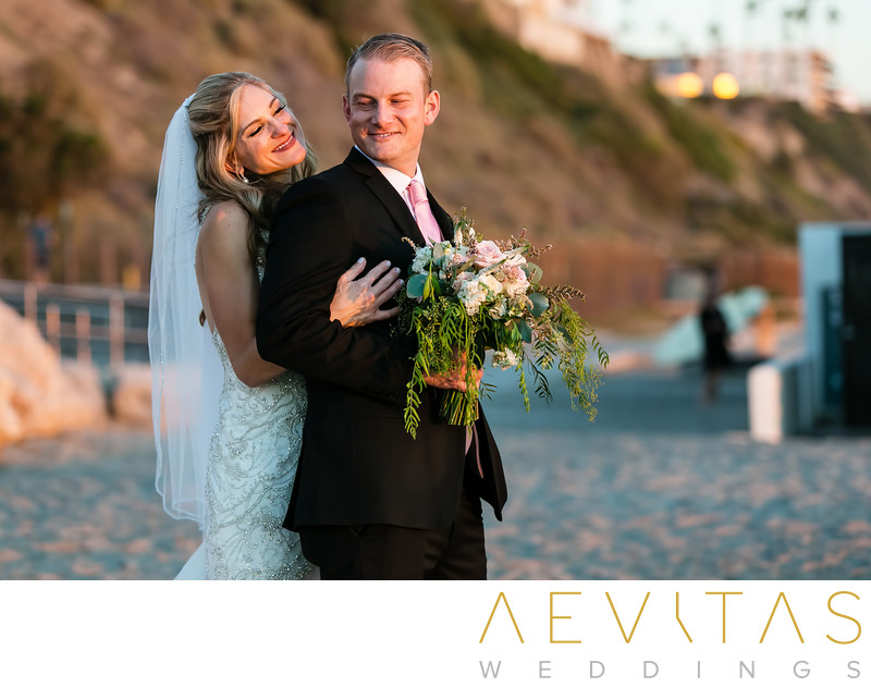 Couple embrace at sunset on San Clemente beach