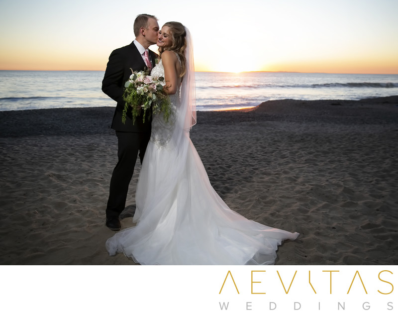 Groom kisses bride's cheek sunset portrait San Clemente
