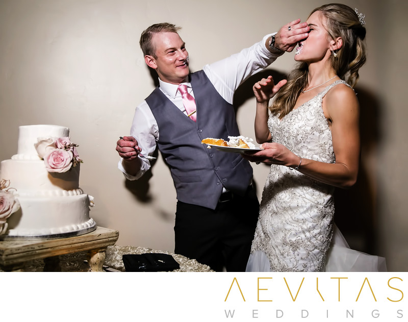 Groom smashing cake in bride's face in San Clemente
