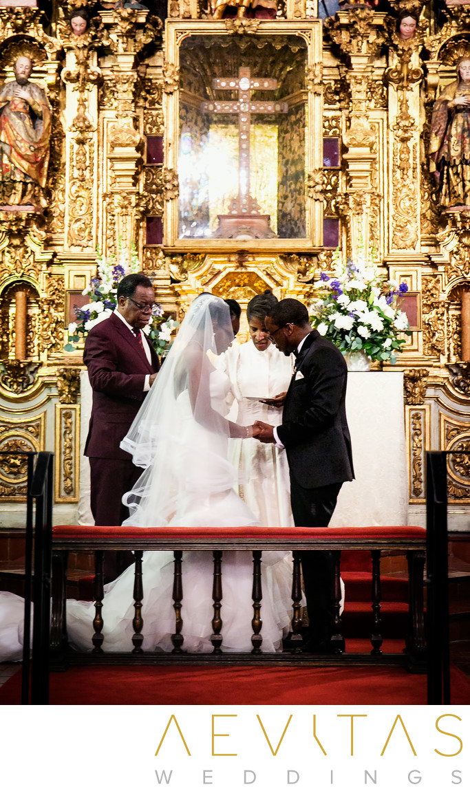 Couple pray in front of gilded altar at Mission Inn