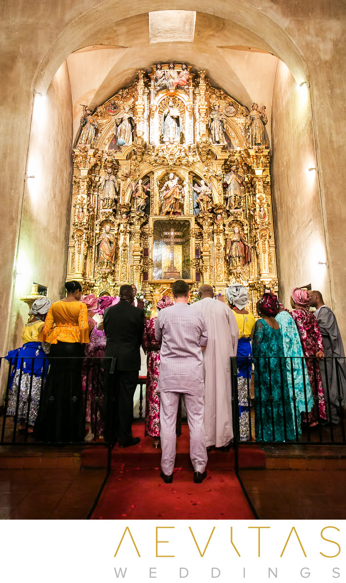 Family pray at gilded altar during Mission Inn wedding