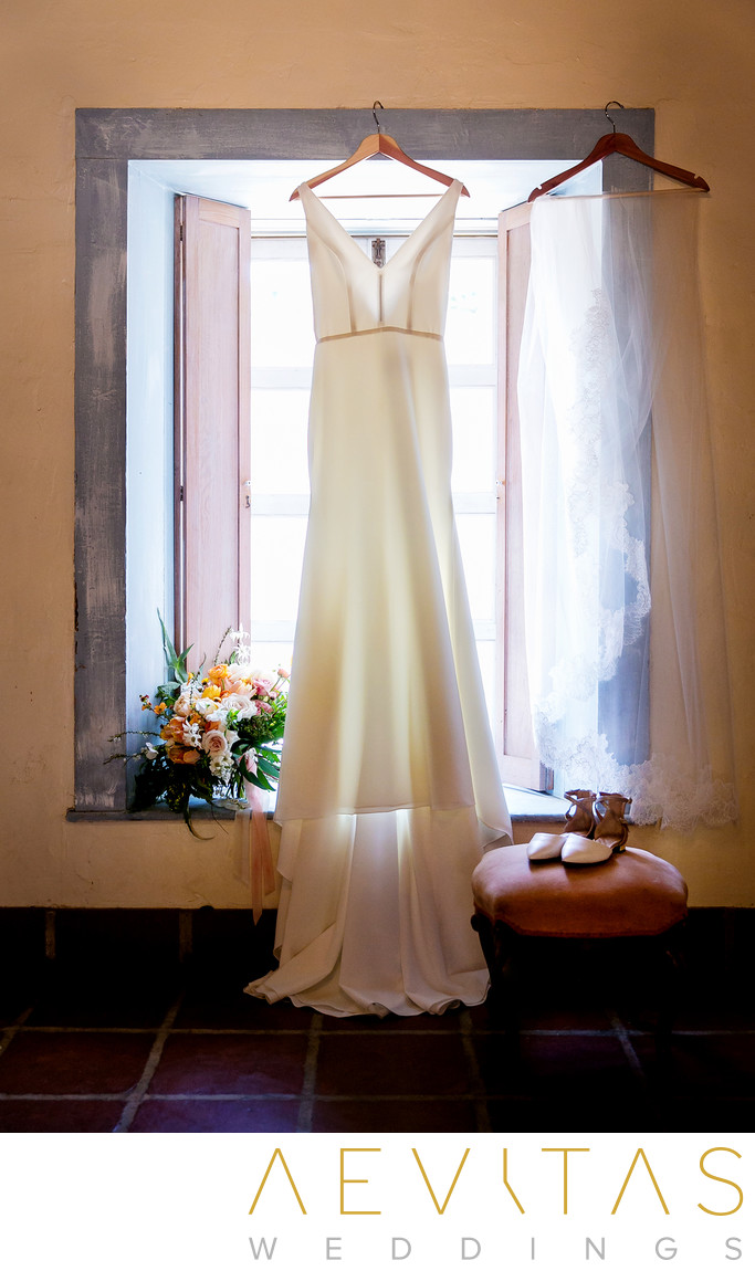 Bridal gown hanging in window at Santa Barbara wedding