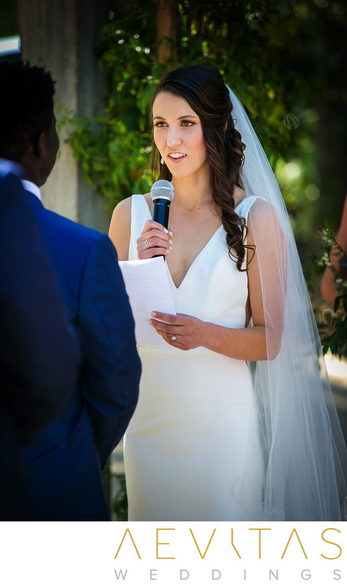 Bride reads vows during garden wedding ceremony