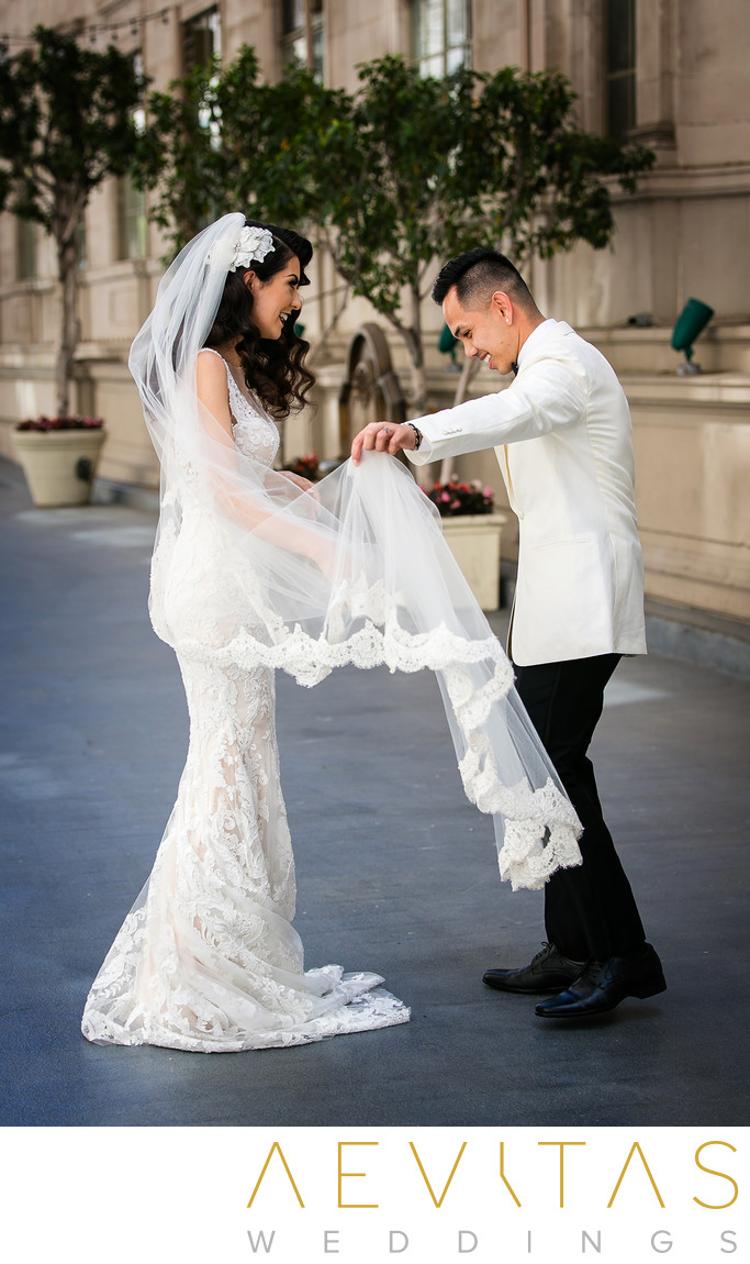 Groom admires bride's lace dress during LA first look