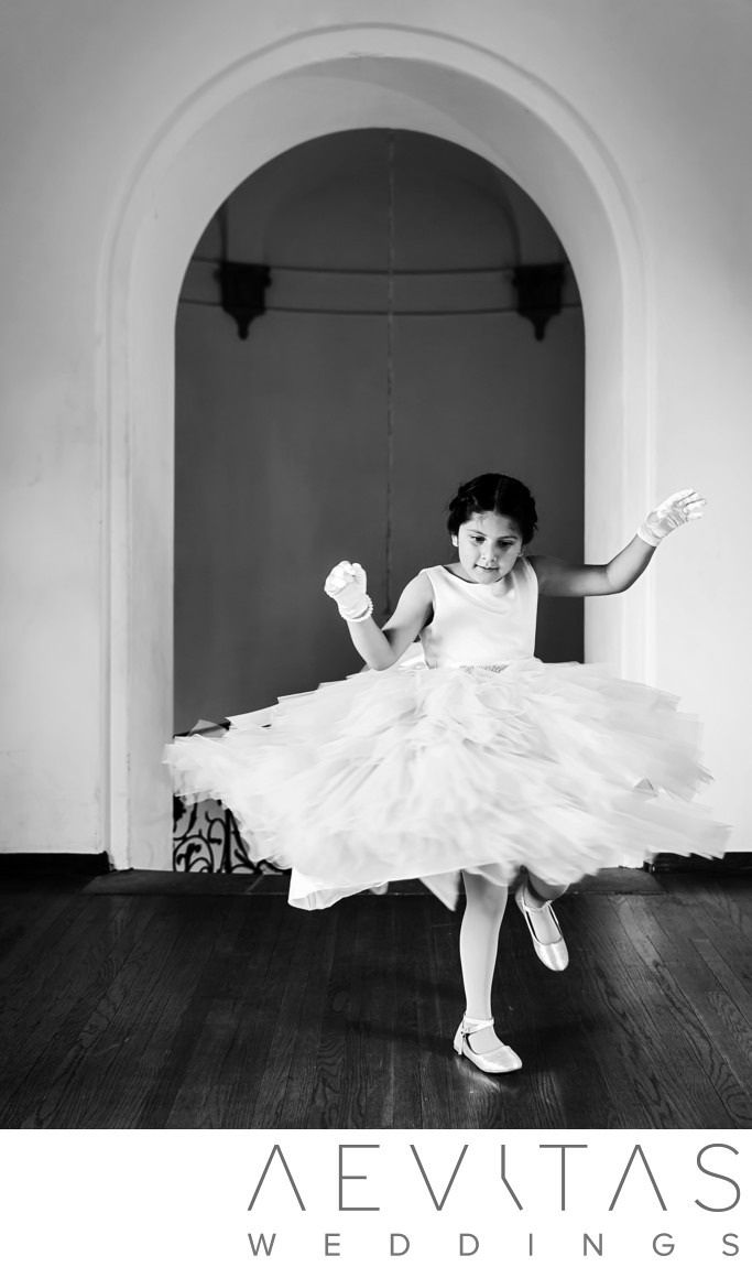 Candid black and white flower girl dancing photo
