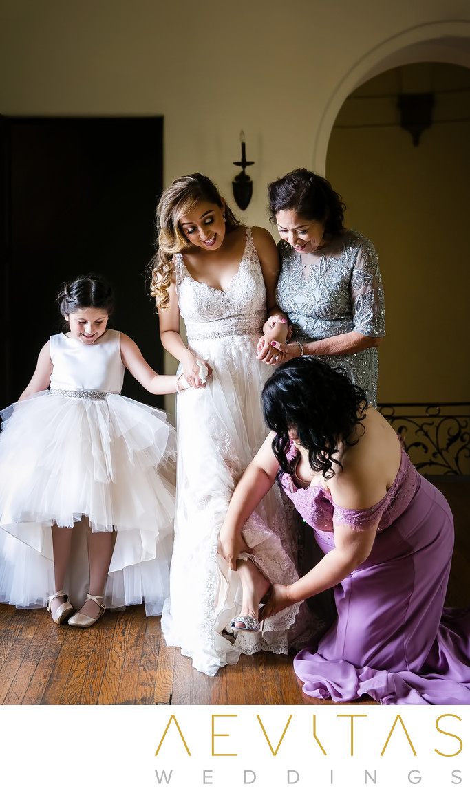 Bridesmaid fixes bride's shoe at Villa Del Sol D'Oro