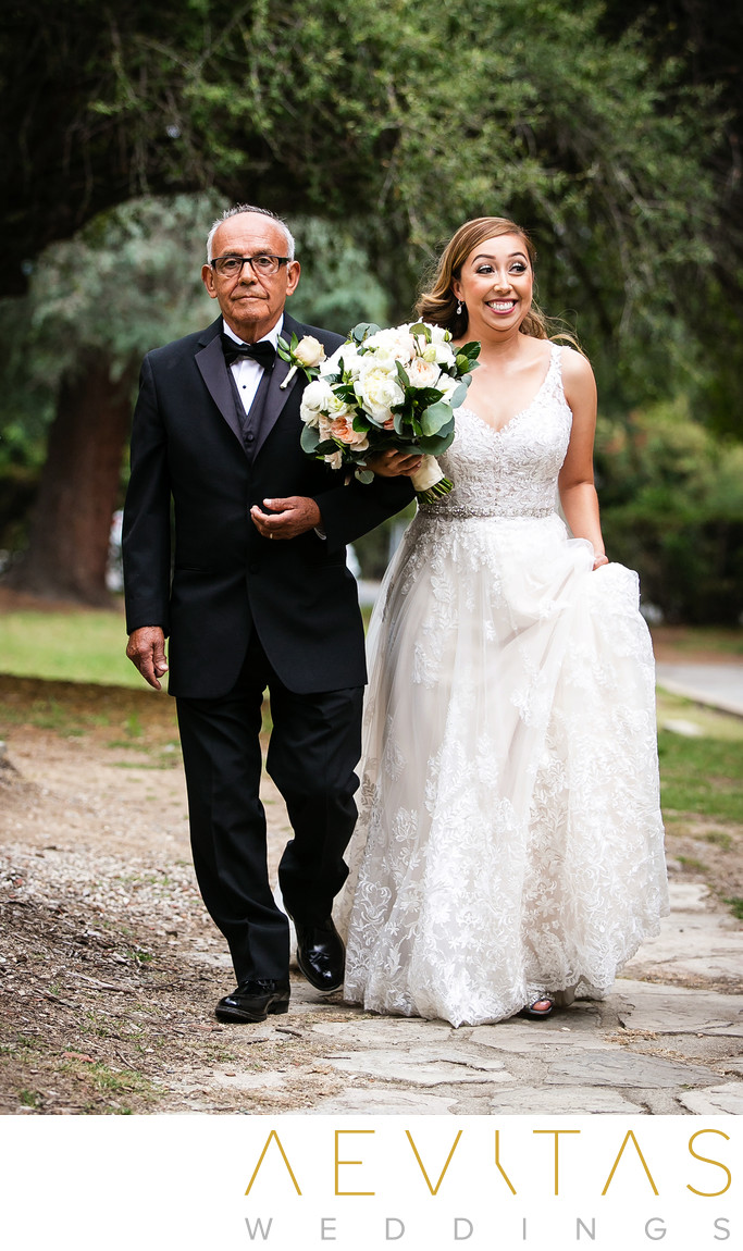 Bride smiles walking down aisle with father