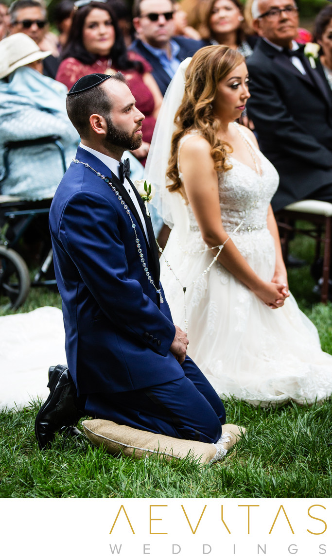 Bride and groom kneel during Catholic wedding