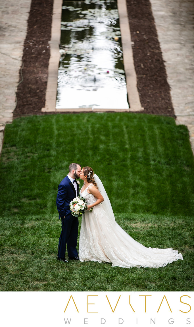 Couple kiss on lawns beside reflecting pool