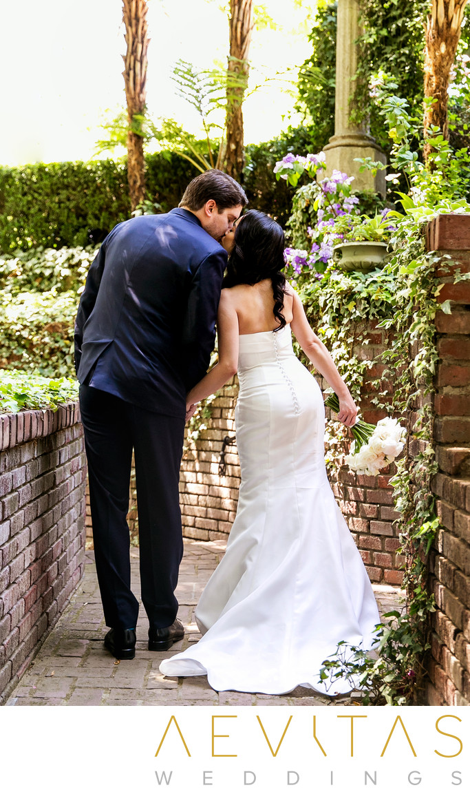 Couple kiss in brick courtyard at The Houdini Estate
