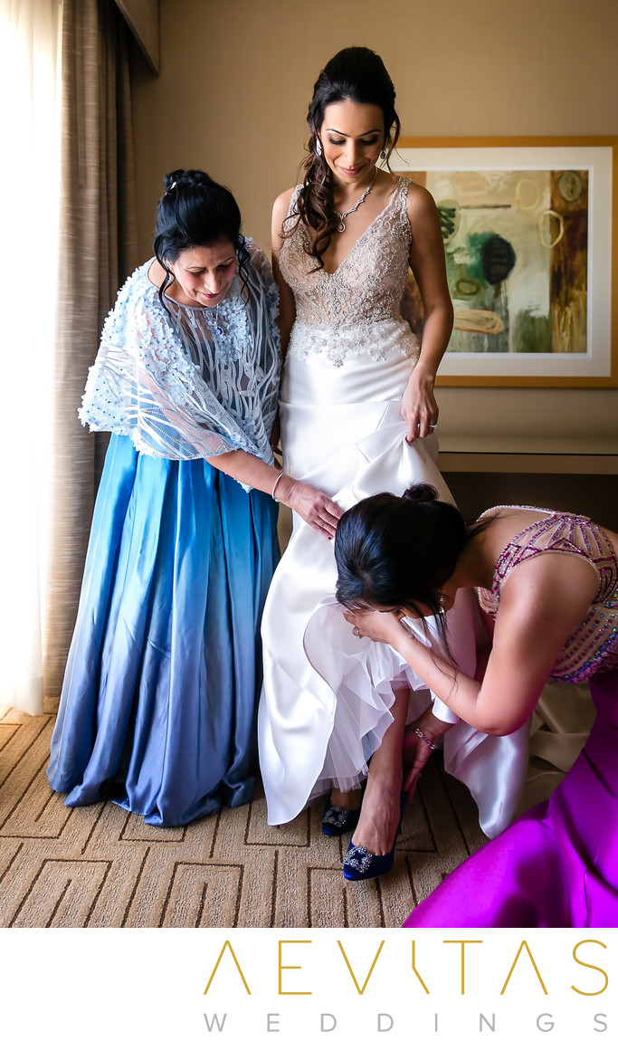 Bride stepping into shoes with mom and sister in Irvine