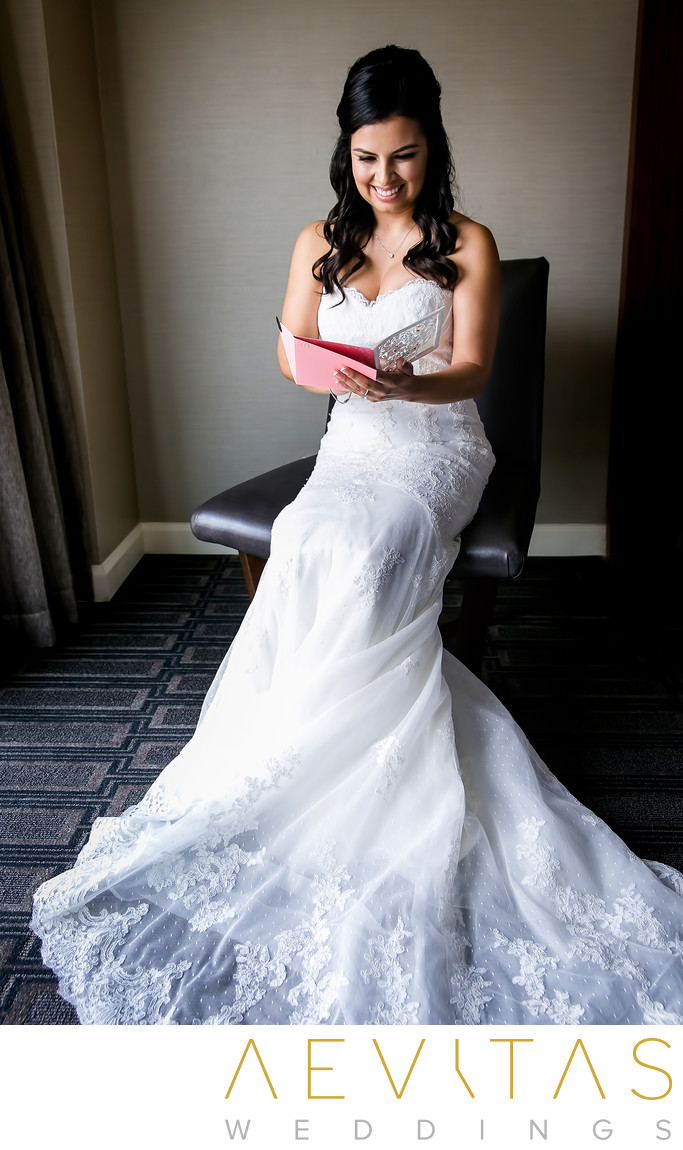 Bride reading note card from groom in Glendale suite