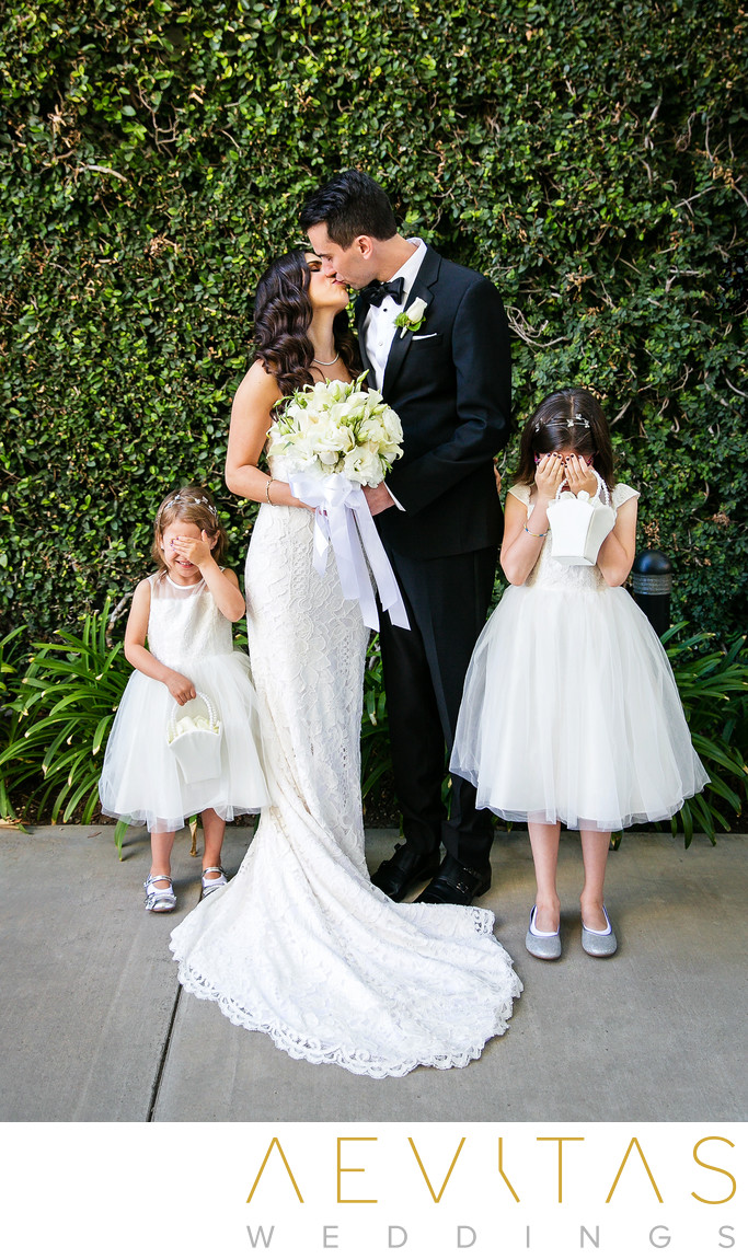 Playful portrait of couple kissing with flower girls