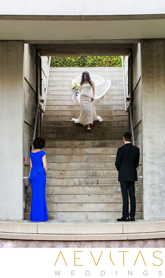 Bride walks down stairs to parents at Skirball wedding