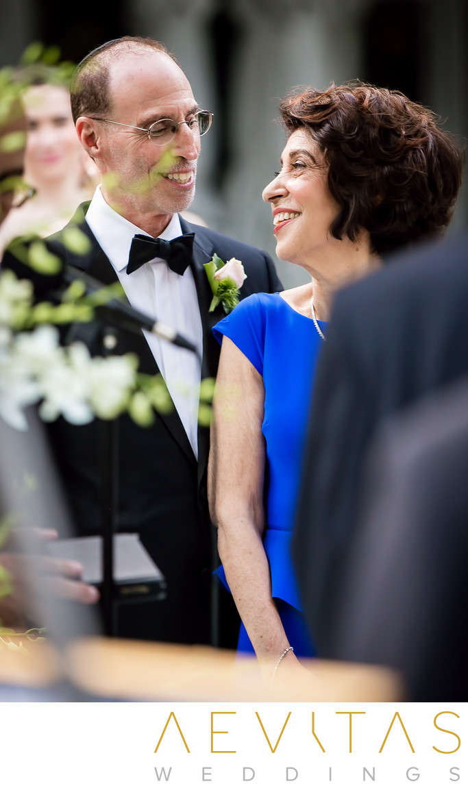 Parents smile at one another during Jewish wedding, LA