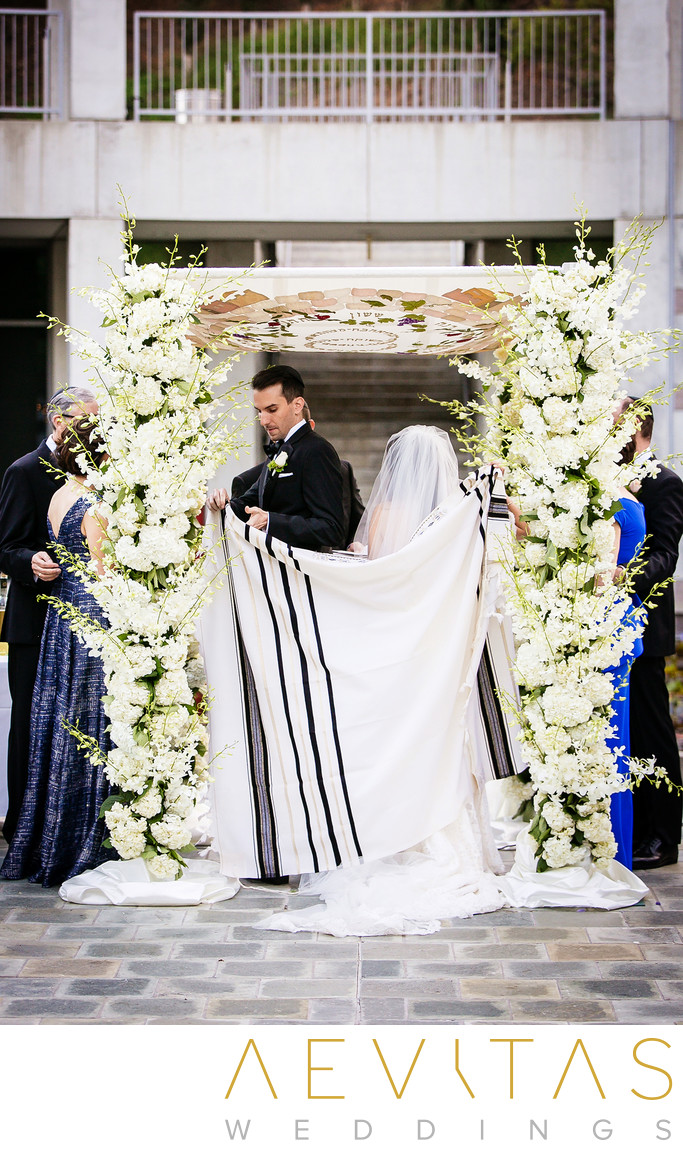 Bride and groom wrapped in cloth at LA Jewish wedding