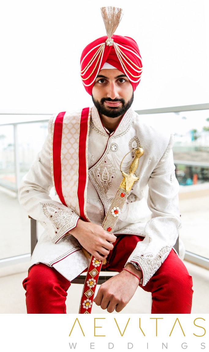 Indian groom portrait with sword on hotel balcony