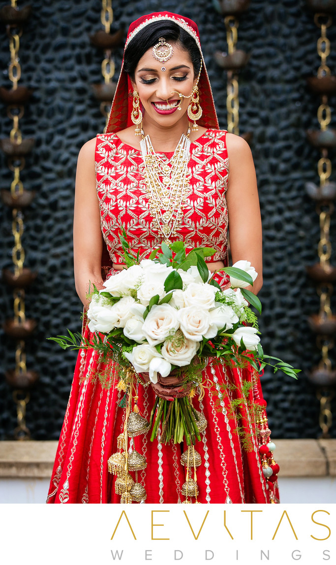 Indian bride in red sari with bouquet of white roses