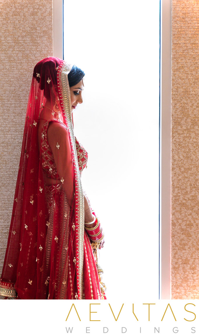 Bride in red sari at Pasea Hotel and Spa window