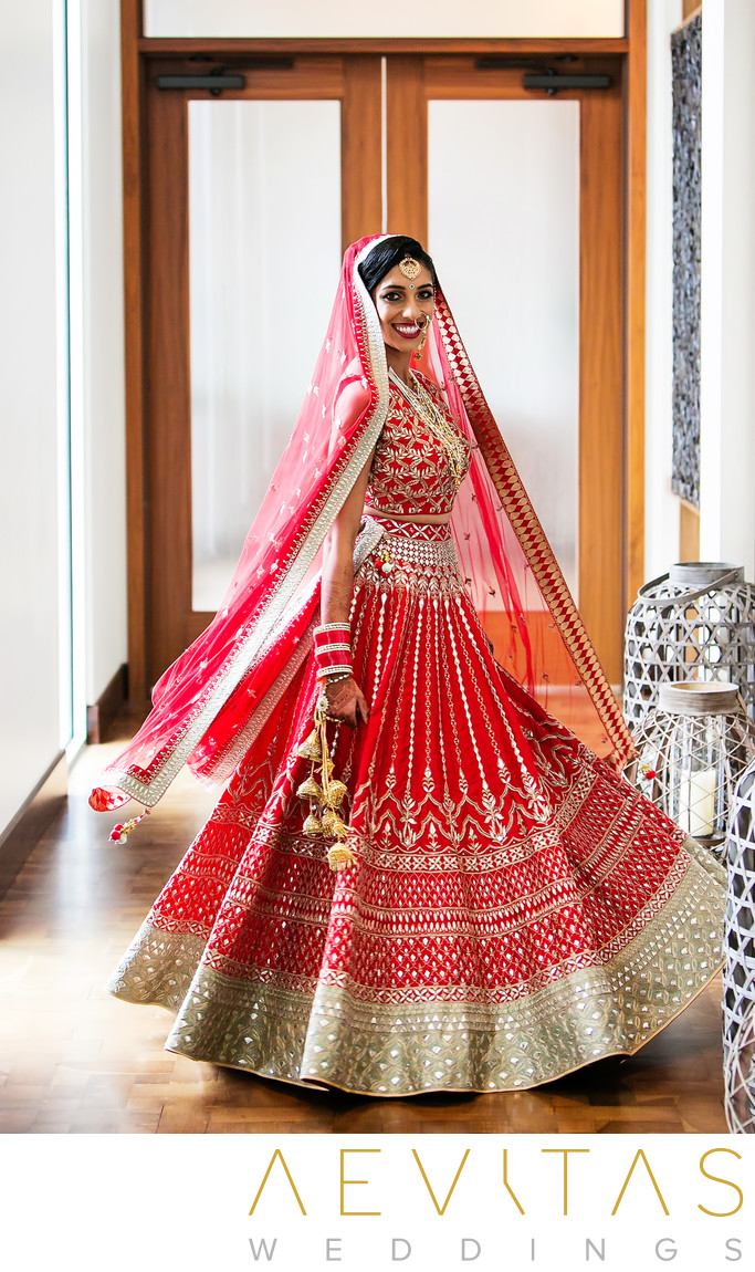 Bride spins in red sari by Indian wedding photographer