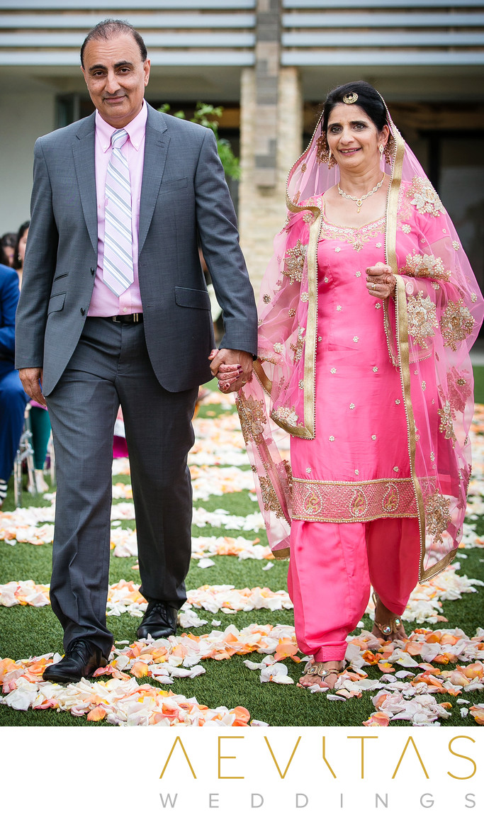 Parents walk down flower-decorated aisle at Pasea Hotel
