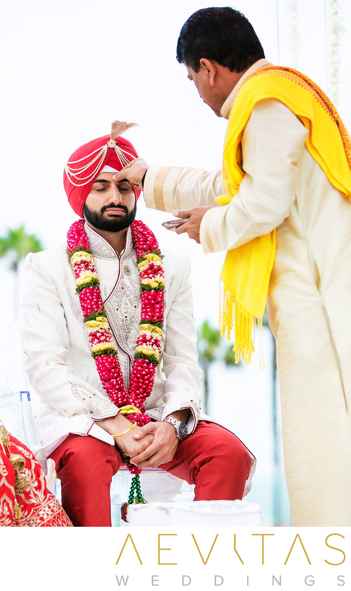 Officiant puts bindi on groom's head at Indian wedding
