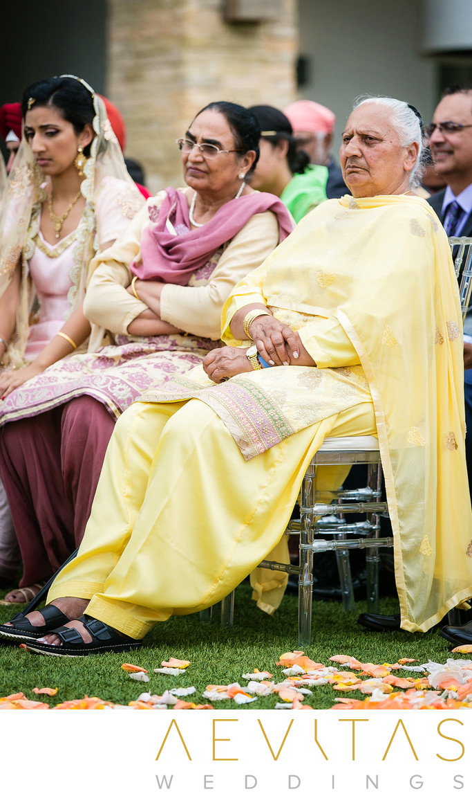 Candid photo of grandmas at Indian wedding ceremony