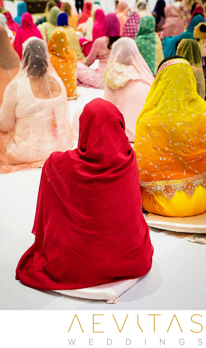Colorful women in saris at Sikh wedding ceremony
