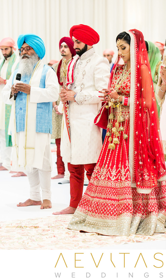 Couple pray with officiant at Sikh wedding ceremony