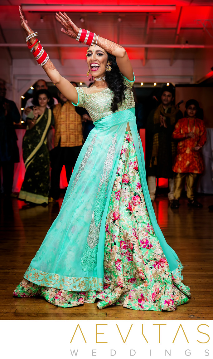 Action shot of bride dancing at Indian wedding party